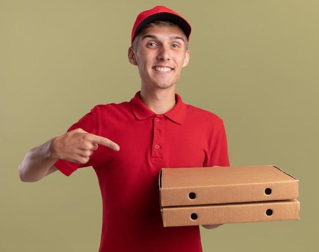 Lächelnder junger blonder lieferjunge hält und zeigt auf pizzakartons