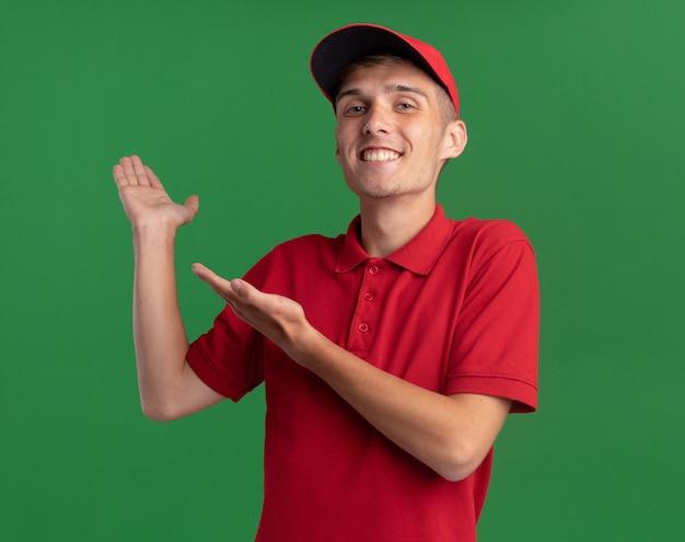 Lächelnder junger blonder lieferjunge zeigt auf leere hand lokalisiert auf grüner wand mit kopienraum