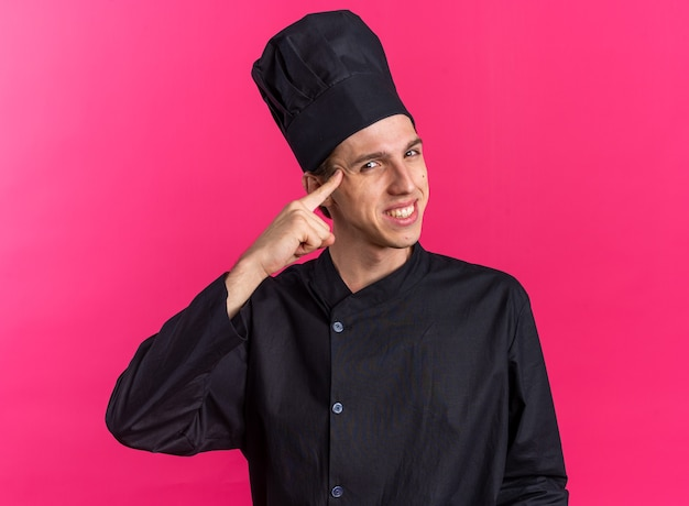 Lächelnder junger blonder männlicher koch in kochuniform und mütze, der denkgeste macht