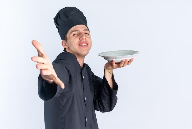 Lächelnder junger blonder männlicher koch in kochuniform und mütze, der in der profilansicht steht und die platte anschaut, die die hand in richtung kamera ausstreckt, isoliert auf weißer wand