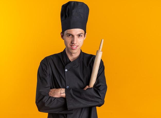 Lächelnder junger blonder männlicher koch in kochuniform und mütze, der mit geschlossener haltung mit nudelholz in die kamera schaut, isoliert auf oranger wand mit kopierraum