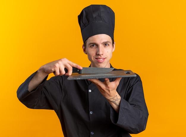 Lächelnder junger blonder männlicher koch in kochuniform und mütze, die das schneidebrett mit dem messer berührt, das auf die kamera isoliert auf der orangefarbenen wand blickt
