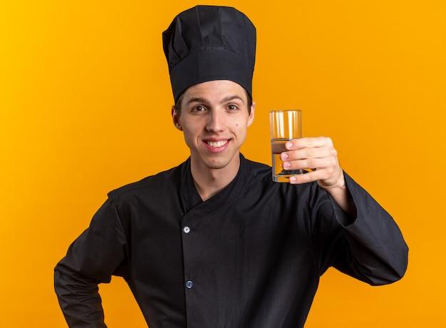 Lächelnder junger blonder männlicher koch in kochuniform und mütze mit blick in die kamera mit einem glas wasser isoliert auf oranger wand