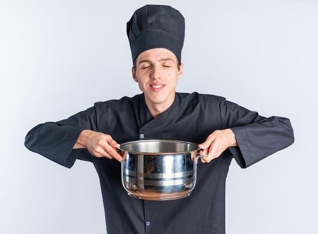Lächelnder junger blonder männlicher koch in kochuniform und mütze mit topf mit geschlossenen augen isoliert auf weißer wand
