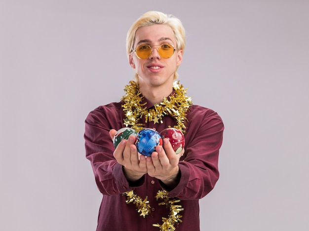 Lächelnder junger blonder mann mit brille mit lametta-girlande um den hals, der weihnachtskugeln in richtung kamera ausstreckt und in die kamera schaut, die auf weißem hintergrund mit kopienraum isoliert ist