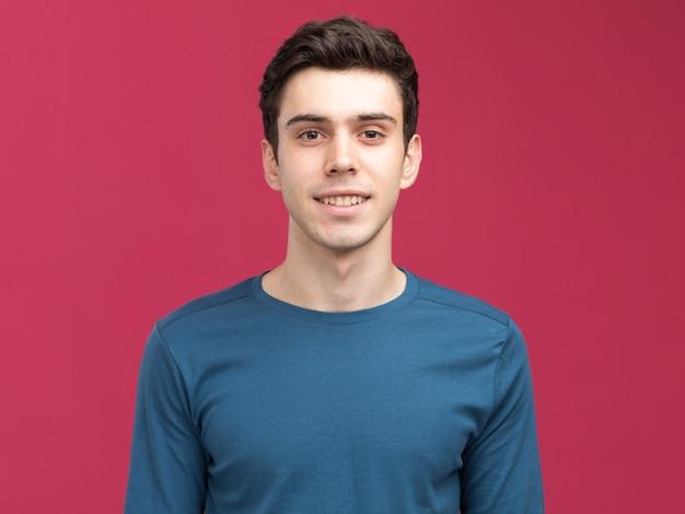 Lächelnder junger brünette kaukasischer mann isoliert auf rosa wand mit kopierraum