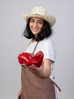 Lächelnder junger brünetter weiblicher gärtner in der uniform, die gartenhut trägt, der rote paprikaschoten lokalisiert auf weißer wand hält