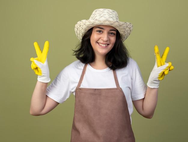 Lächelnder junger brünetter weiblicher gärtner in der uniform, die gartenhut und handschuhe trägt, gestikuliert siegeshandzeichen mit zwei händen, die auf olivgrüner wand lokalisiert werden