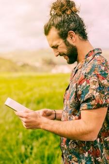 Lächelnder junger brunettemann, der mit tablette auf dem gebiet steht