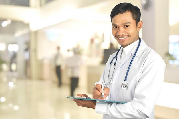 Lächelnder junger doktor, der ein klemmbrett auf krankenhaus hält