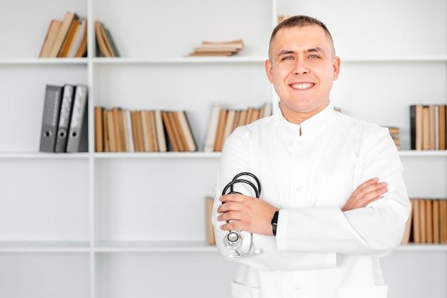 Lächelnder junger doktor, der ein stethoskop anhält