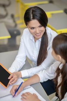 Lächelnder junger dunkelhaariger lehrer, der tablett erzählen und schulmädchen während der schulstunde zeigt