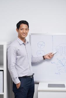 Lächelnder junger finanzmanager, der diagramme und diagramme auf weißem brett zeigt