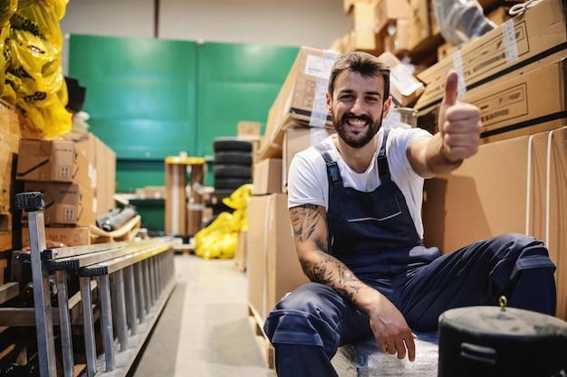 Lächelnder junger fleißiger tätowierter bärtiger arbeiter in overalls, die im lager sitzen, umgeben von kisten und daumen hoch
