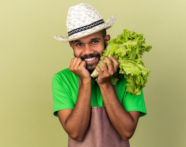 Lächelnder junger gärtner afroamerikanischer mann mit gartenhut mit salat isoliert auf olivgrüner wand