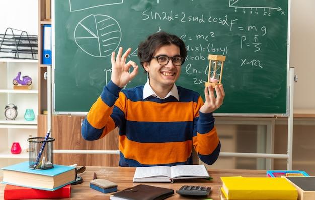 Lächelnder junger geometrielehrer mit brille, der am schreibtisch mit schulmaterial im klassenzimmer sitzt und eine sanduhr hält, die nach vorne schaut und ein gutes zeichen macht