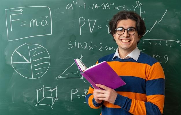 Lächelnder junger geometrielehrer mit brille, der im klassenzimmer vor einer tafel steht und ein offenes buch hält, das nach vorne schaut