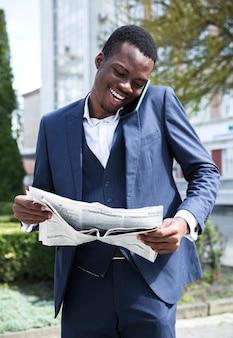 Lächelnder junger geschäftsmann, der am handy liest die zeitung spricht