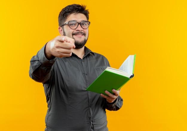 Lächelnder junger geschäftsmann, der brille hält buch hält und sie geste lokalisiert auf gelber wand zeigt