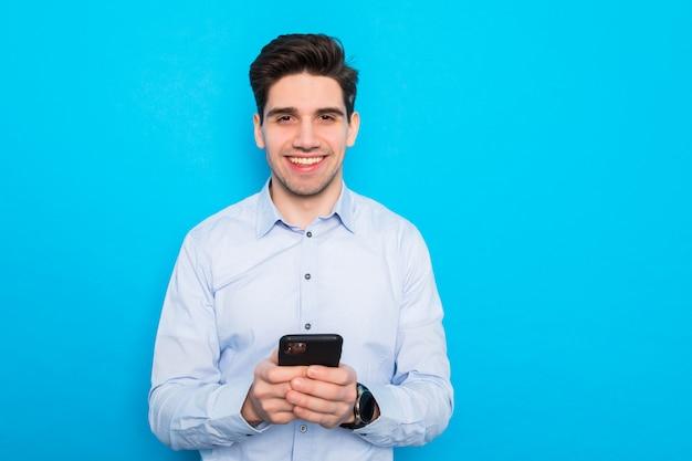 Lächelnder junger geschäftsmann, der handy hält und bildschirm lokalisiert auf blauem studioraum betrachtet.