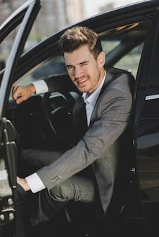 Lächelnder junger geschäftsmann, der im auto mit einer offenen tür sitzt