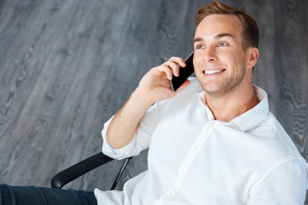 Lächelnder junger geschäftsmann, der im büro am handy sitzt und spricht