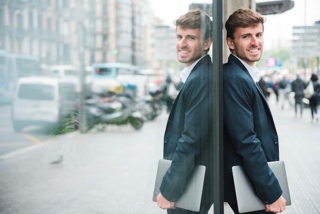 Lächelnder junger geschäftsmann, der in der hand den handy sich lehnt auf glaswand hält