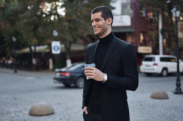 Lächelnder junger geschäftsmann, der mit kaffee zur arbeit geht