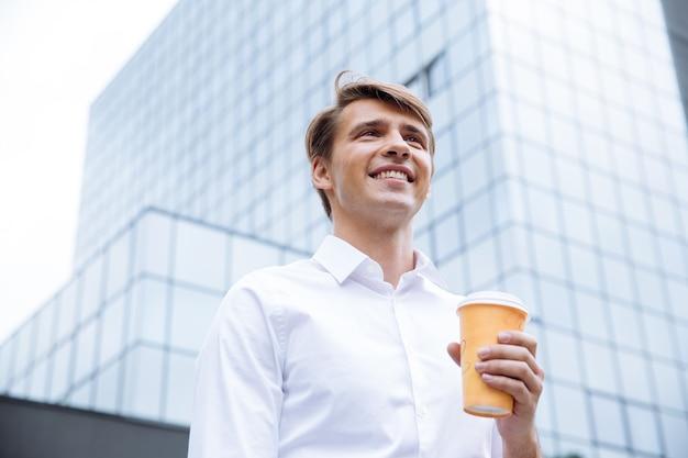 Lächelnder junger geschäftsmann, der nahe geschäftszentrum steht und kaffee trinkt