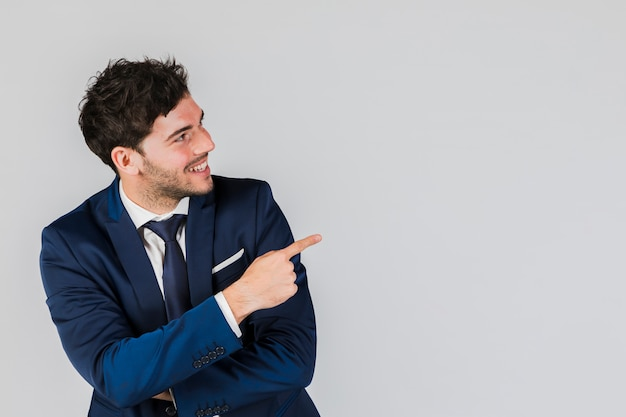 Lächelnder junger geschäftsmann, der seinen finger gegen grauen hintergrund zeigt
