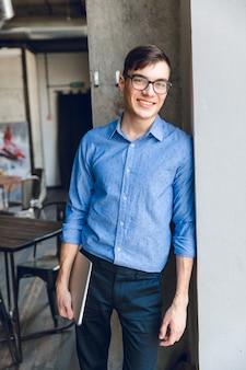 Lächelnder junger geschäftsmann lehnt sich an graue wand an, die laptop in der hand hält