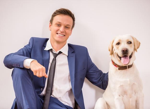 Lächelnder junger geschäftsmann mit seinem hund, der auf boden sitzt.