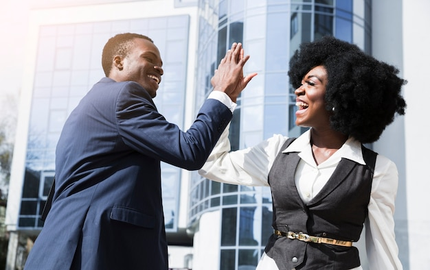 Lächelnder junger geschäftsmann und geschäftsfrau, die hoch fünf vor unternehmensgebäude geben