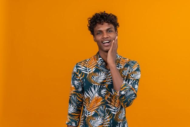 Lächelnder junger gutaussehender dunkelhäutiger mann mit dem lockigen haar im blatt druckte hemd, das hand auf wange auf einem orangefarbenen hintergrund hält
