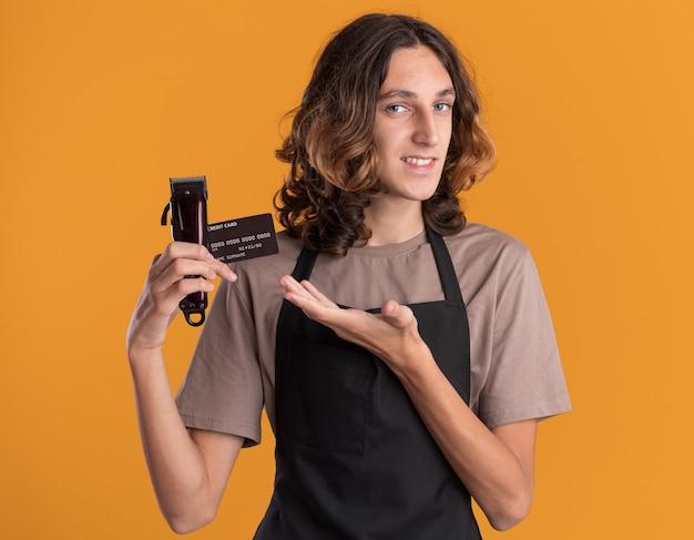 Lächelnder junger gutaussehender friseur in uniform, der mit der hand auf kreditkarte und haarschneidemaschinen zeigt, die auf der vorderseite isoliert auf der orangefarbenen wand stehen