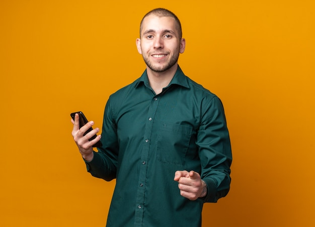 Lächelnder junger gutaussehender kerl, der ein grünes hemd trägt, das telefon hält und nach vorne zeigt?