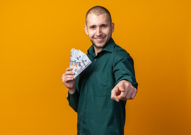 Lächelnder junger gutaussehender kerl, der ein grünes hemd trägt und bargeld hält, das dir geste zeigt
