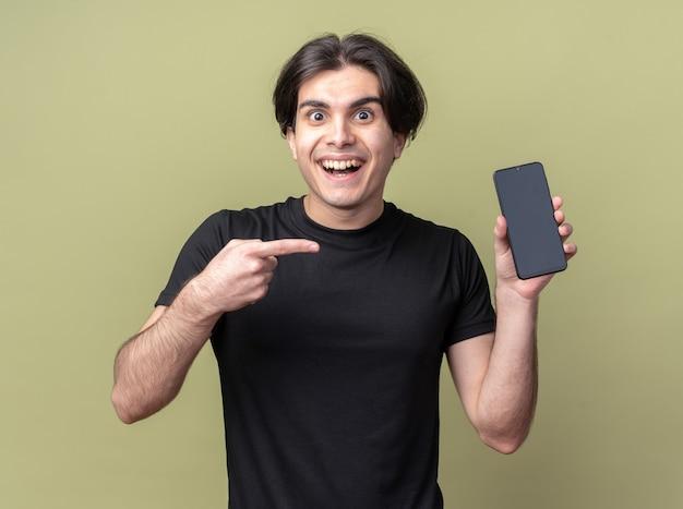 Lächelnder junger gutaussehender kerl, der ein schwarzes t-shirt trägt und auf das telefon zeigt, isoliert auf olivgrüner wand?