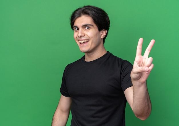 Lächelnder junger gutaussehender kerl, der ein schwarzes t-shirt trägt und eine friedensgeste zeigt, die auf grüner wand mit kopienraum isoliert ist?