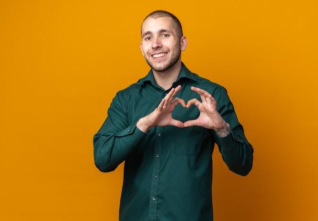 Lächelnder junger gutaussehender kerl, der grünes hemd mit herzgeste trägt