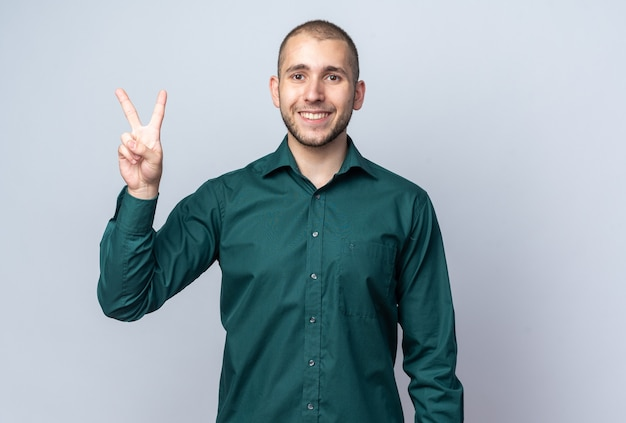 Lächelnder junger gutaussehender kerl, der grünes hemd trägt, das friedensgeste zeigt