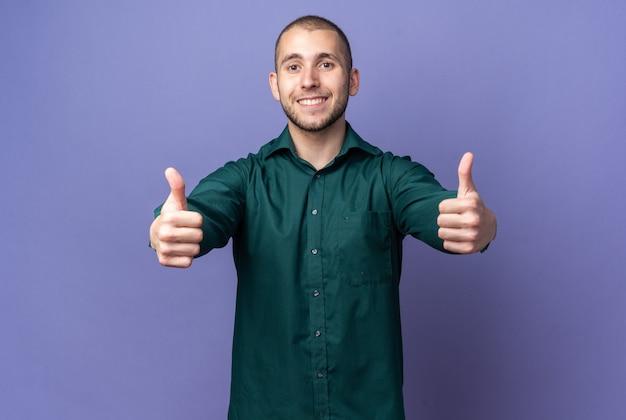 Lächelnder junger gutaussehender kerl, der grünes hemd trägt und daumen nach oben zeigt