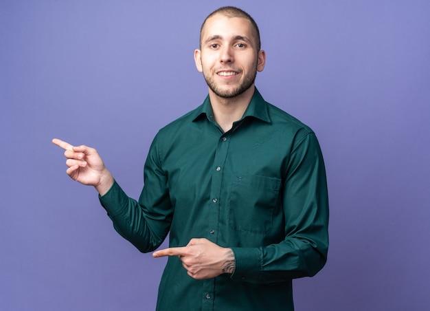 Lächelnder junger gutaussehender kerl, der grünes hemd trägt, zeigt an der seite?