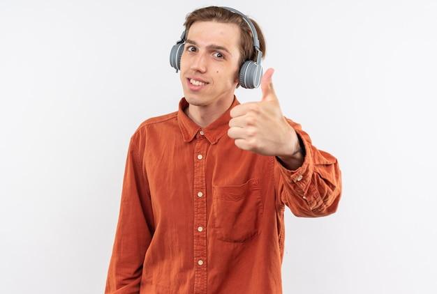 Lächelnder junger gutaussehender kerl, der rotes hemd mit kopfhörern trägt, die daumen nach oben zeigen