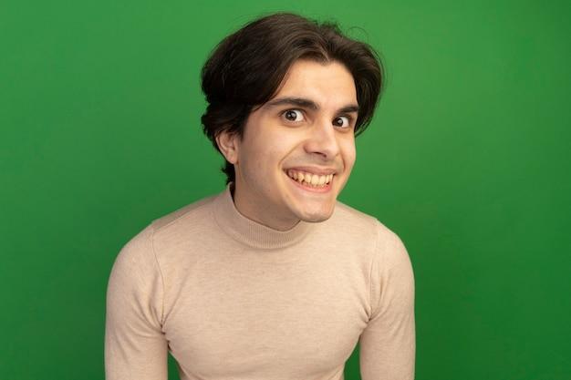 Lächelnder junger gutaussehender kerl isoliert auf grüner wand