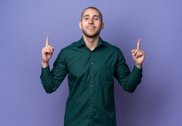 Lächelnder junger gutaussehender kerl mit grünem hemd zeigt nach oben