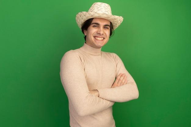 Lächelnder junger gutaussehender kerl mit hut, der die hände isoliert auf grüner wand kreuzt
