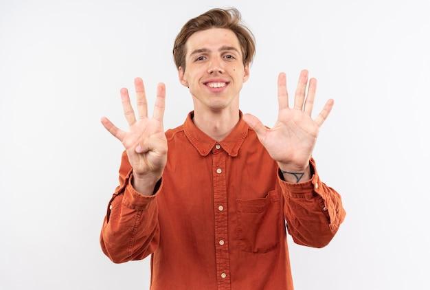 Lächelnder junger gutaussehender kerl mit rotem hemd, das verschiedene zahlen zeigt