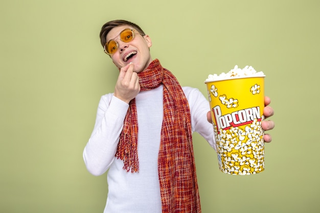 Lächelnder junger gutaussehender kerl mit schal mit brille, der popcorn-eimer hält