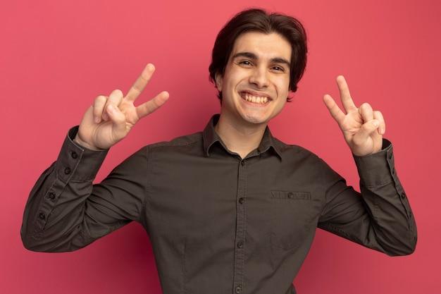 Lächelnder junger gutaussehender kerl mit schwarzem t-shirt mit friedensgeste isoliert auf rosa wand
